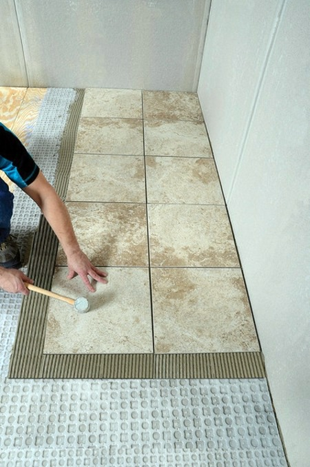 Laying floor tile in bathroom